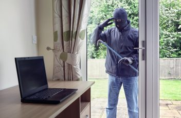 Thief looking through patio doors window at a laptop computer to steal