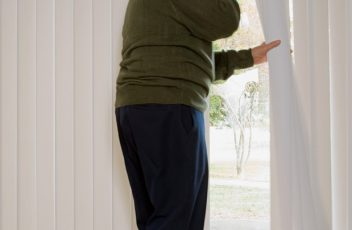 Elderly man on phone and looking out of window